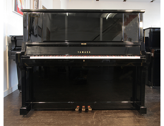 A hand-built, 1980, Yamaha YUA upright piano with a black case and brass fittings