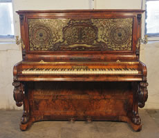A Burling & Burling upright piano with a burr walnut case. Cabinet features an ornate fretwork front panel, moveable brass candlesticks and carved, cabriole legs