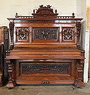 Piano for sale. A Gabel upright piano with an ornately carved, Neoclassical style, walnut case. Cabinet features carvings of acanthus, lions, arabesques and flowers in high relief. Piano pediment features reclining cherubs with sheet music.