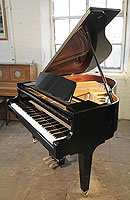 A 2014, Kawai GM-10K baby grand piano with a black case and square, tapered legs