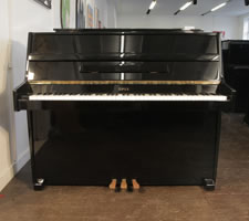An Opus upright piano with a black case. Piano has a seven octave keyboard three pedals.