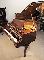A Petrof grand piano with a walnut case and cabriole legs