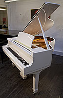 A brand new Steinhoven Model 148 baby grand piano with a white case and spade legs
