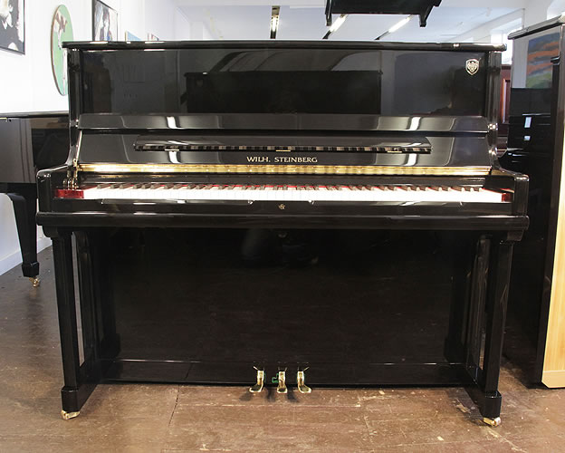 A Brand New Steinberg Model AT-K23 upright piano with a black case and brass fittings. Piano features a slow fall mechanism, eighty-eight note keyboard and three pedals.