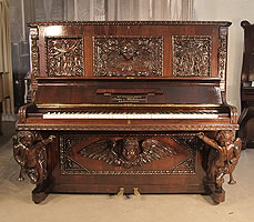 A Leitter & Winkelmann upright piano with an ornately, carved rosewood case. Cabinet appears to blend disparate design styles of the Medieval and Rococo. Front panels and pilasters are naively carved with creation myth scenes of Adam and Eve. The lower half of the piano exhibits more of a Rococo influence. The piano legs are elegantly carved, cherub caryatids.