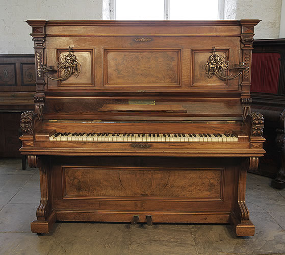 Antique, Ehret upright piano with a  walnut case. Cabinet features piano cheeks with carved lions heads