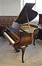 Piano for sale. A 1940, Feurich baby grand piano with a walnut case and cabriole legs.