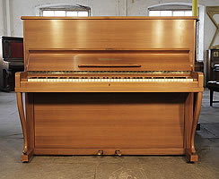 A 1962, Grotrian Steinweg 120 upright piano with a polished, walnut case. Piano has an eighty-eight note keyboard and two pedals
