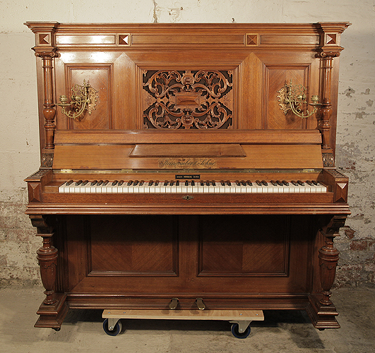 An 1897, Steingraeber upright piano with a walnut case, carved filgree panel and ornate brass candlesticks