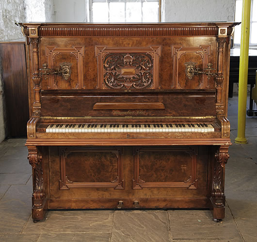An 1898, Steingraeber upright piano with a walnut case, Neoclassical style, carvings and ornate brass candlesticks