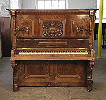 An 1898, Steingraeber upright piano with a walnut case, Cabinet features a carved, Neoclassical style filgree panel and ornate brass candlesticks