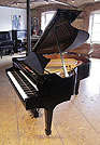 A 1922, Steinway Model M grand piano with a black case and spade legs. Piano has an eighty-eight note keyboard and a two-pedal lyre.