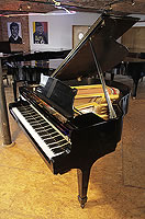 A restored, 1956, Steinway Model S baby grand piano with a black case and spade legs.