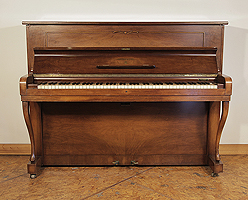 A 1954, Steinway Model Z upright piano with a mirrored, walnut case and cabriole legs.