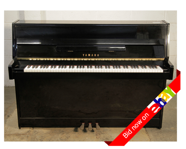A 1991, Yamaha C108 upright piano with a black case and brass fittings