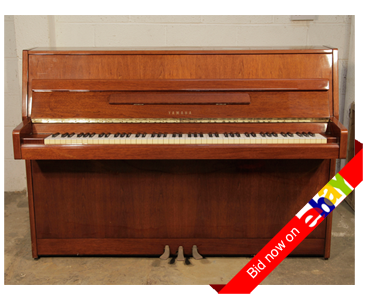A 1984, Yamaha MJ5 upright piano with a walnut case and brass fittings