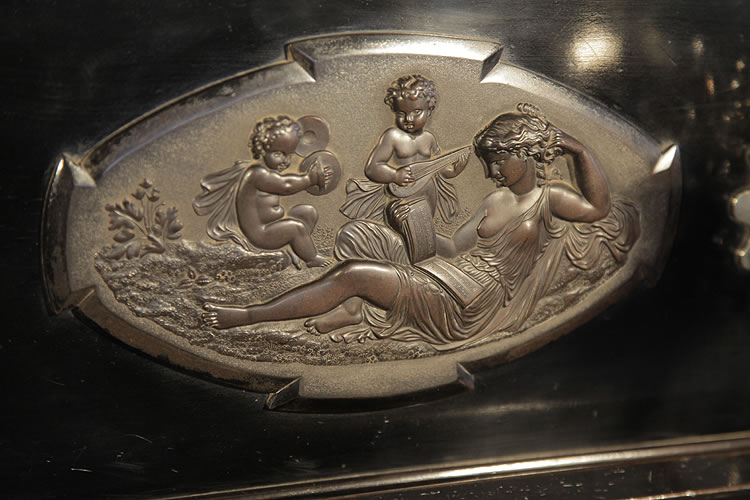 Bord plaque featuring a reclining lady and cherubs playing instruments