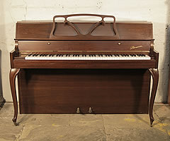 A 1980, Danemann console upright piano with a mahogany case and cabriole legs.
