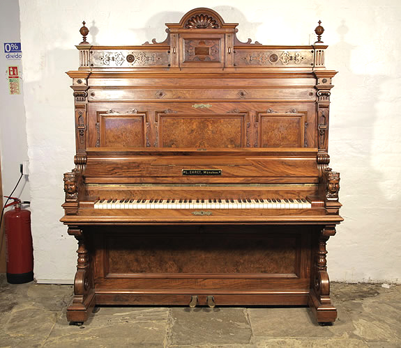 Antique, Ehret upright piano with a walnut case. Cabinet features piano cheeks with carved female heads