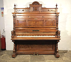 Antique, Ehret upright piano with a walnut case. Cabinet features piano cheeks with carved female heads and carved pediment with orbs