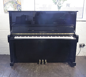A 1985, Kawai NS-10 upright piano with a black case and polyester finish. Piano has an eighty-eight note keyboard and three pedals.