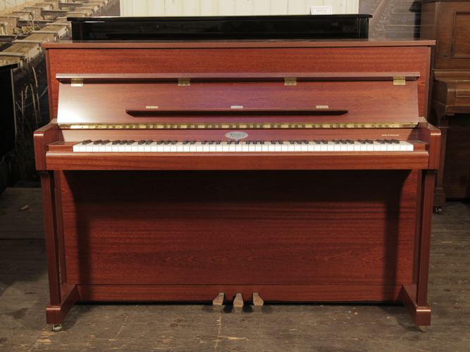 A Kemble upright piano with a polished, mahogany case