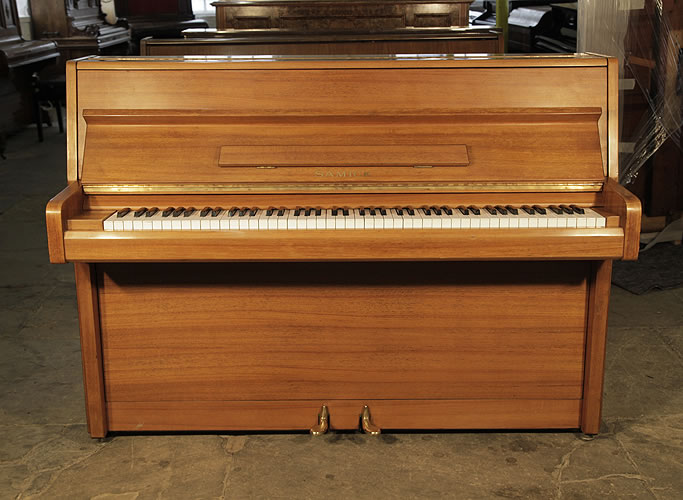 A 1986, Samick upright piano with a polished, walnut case