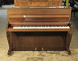 A 1964, Schimmel upright piano with a mahogany case and cabriole legs