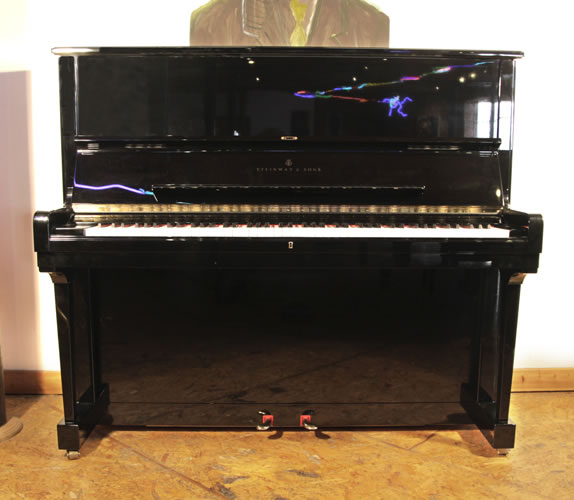 Piano for sale. A 1995, Steinway Model K upright piano with a black case and brass fittings. Piano has an eighty-eight note keyboard and two pedals