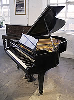 A 1936, Steinway Model M grand piano with a black case and spade legs