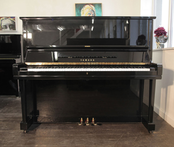 A 1973, Yamaha U3 upright piano with a black case and brass fittings