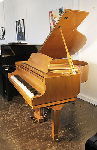 Piano for sale. A Carlmann baby grand piano with a walnut case and spade legs