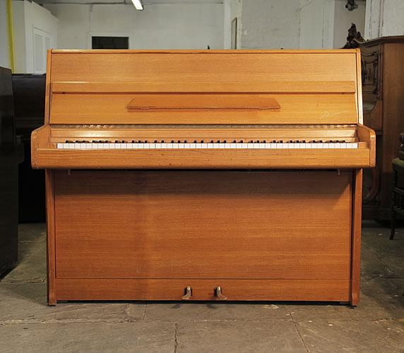 A Danemann upright piano with a teak case