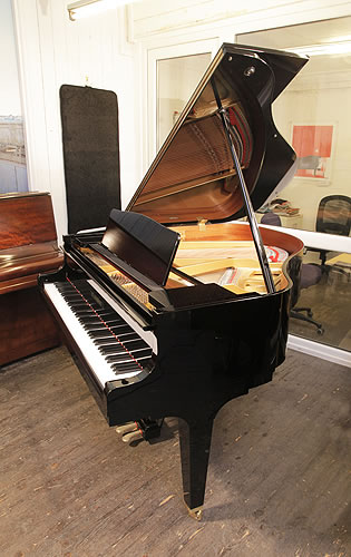 Piano for sale. A 2017, Kawai GM10 baby grand piano for sale with a black case and square, tapered legs