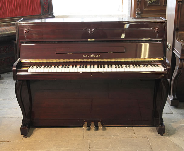 A Karl Muller upright piano with a mahogany case and cabriole legs