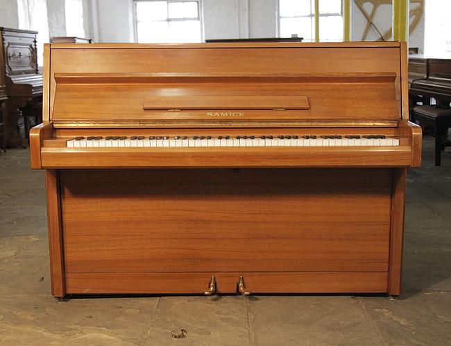 A Samick upright piano with a polished, teak case