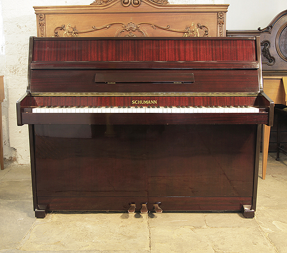A Schumann upright piano with a mahogany case and polyester finish