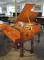 A 1908, Steinway with a satinwood case, hand-painted with Berainesque decoration featuring arabesques, flowers, urns, swags, bows, musical instruments and plaques with cherubs and reclining ladies. Piano legs and lyre are attached with a sinuous, cross stretcher. Cabinet designed and made by the renowned Waring and Gillow.