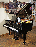 A 1970 Steinway Model A grand piano with a walnut case and spade legs. Piano has an eighty-eight note keyboard and a three-pedal lyre.