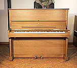 Piano for sale. A 1985, Steinway Model K upright piano with a polished, oak case.. Piano has an eighty-eight note keyboard and two pedals