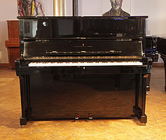 A 1985, Steinway Model V upright piano with a black case and brass fittings