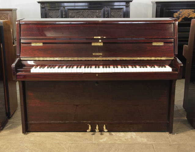 A Wesberg upright piano with a mahogany case and polyester finish