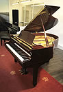 Piano for sale. A 1993, Yamaha grand piano with a mahogany case. Piano has an eighty-eight note keyboard and a three-pedal lyre.
