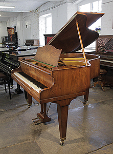A 1937, Bechstein Model S baby grand piano with a satin, figured walnut case and tapered legs..