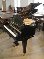 A pre-owned, Bechstein Model S baby grand piano with a black case and tapered legs