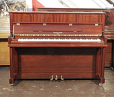 A brand new, Besbrode SU112 upright piano with a mahogany case and polyester finish