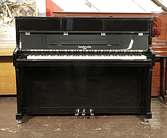 A brand new, Besbrode SU113 upright piano with a black case and chrome fittings. Piano features a slow fall mechanism