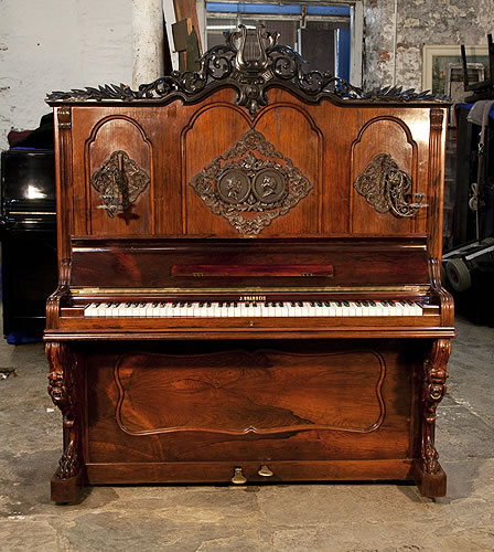 Brandeis upright piano for sale with a rosewood case and reverse scroll, claw foot legs. Front panel features ornately carved plaques with heads of Beethoven and Mozart. Carved pediment features a central harp surrounded by scrolling acanthus and laurel.