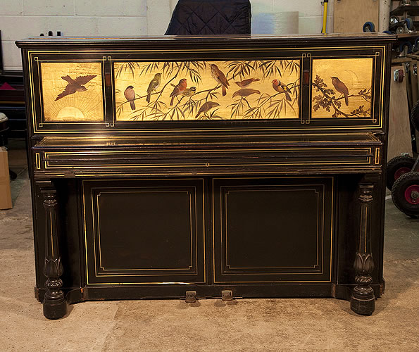 An 1880's Broadwood upright piano for sale with an ebonised case with brass stringing inlay accents. Cabinet features a  front panel exquisitely hand-painted with a variety of songbirds on a gold ground.