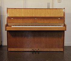 Dorffman upright piano with a walnut case. Piano has an eighty-eight note keyboard and three pedals.